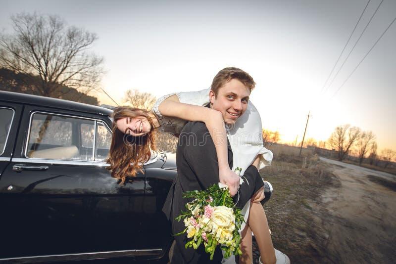 Pares hermosos de la boda en el campo al lado del coche retro el novio del hombre está tomando deteniendo a la novia en sus brazo imagen de archivo libre de regalías