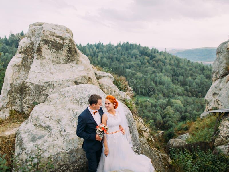 Pares hermosos de la boda en el paisaje rocoso maravilloso del fondo de las montañas de Cárpatos imagen de archivo