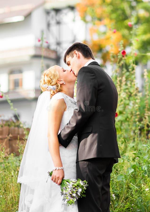 Pares hermosos de la boda en parque Besan y se abrazan fotografía de archivo