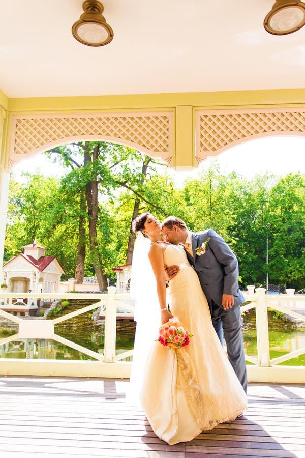 Pares hermosos de la boda en parque Beso y abrazo imagenes de archivo