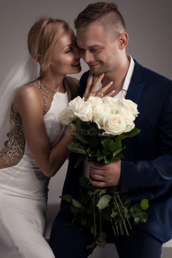 Pares hermosos de la boda que presentan en estudio imagen de archivo libre de regalías