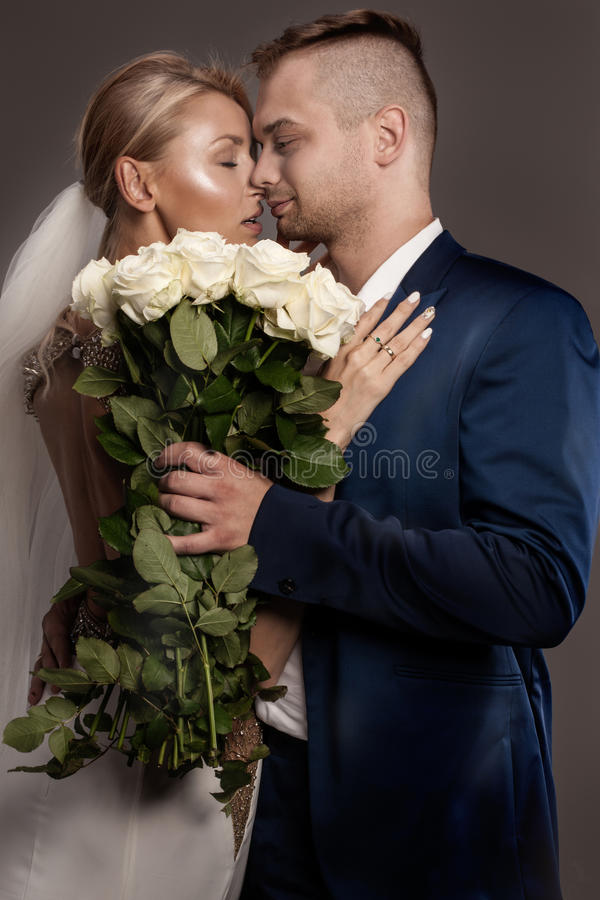 Pares hermosos de la boda que presentan en estudio imagen de archivo
