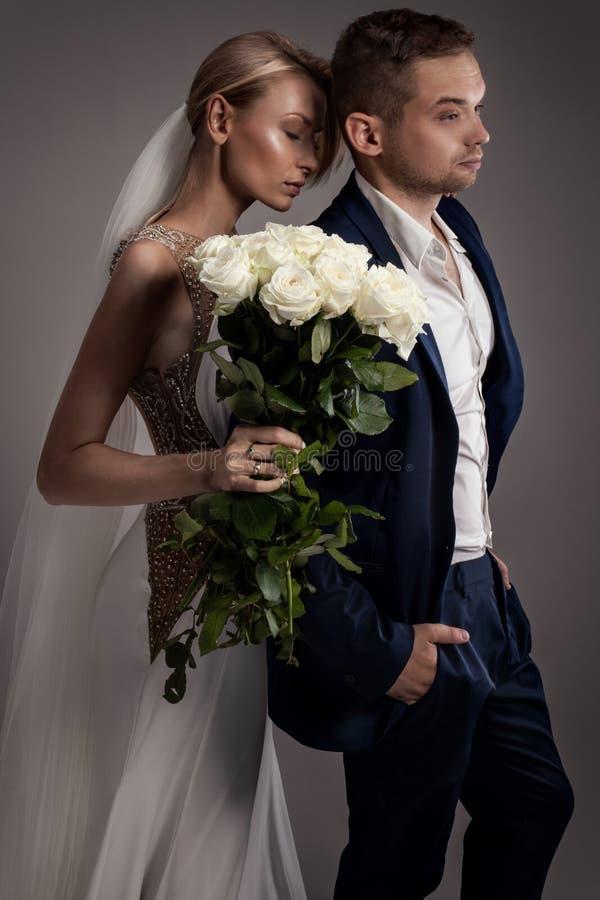 Pares hermosos de la boda que presentan en estudio fotos de archivo