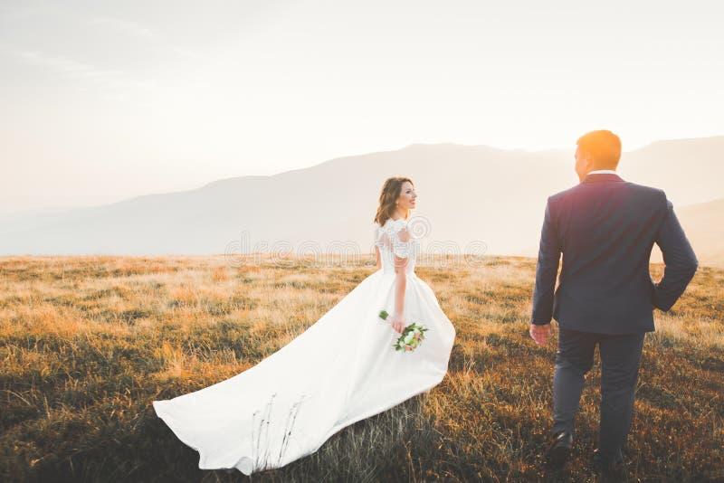Pares hermosos de la boda que presentan encima de una montaña en la puesta del sol imagen de archivo libre de regalías