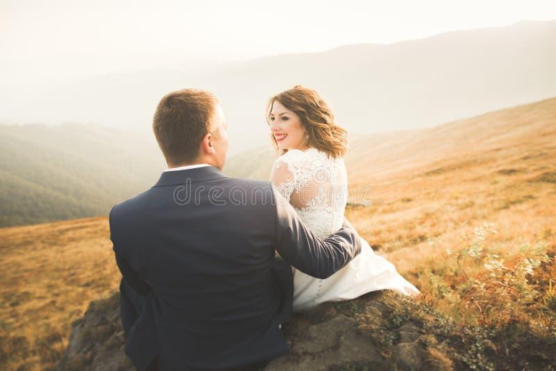 Pares hermosos de la boda que se besan y que abrazan cerca de la montaña con la visión perfecta fotografía de archivo