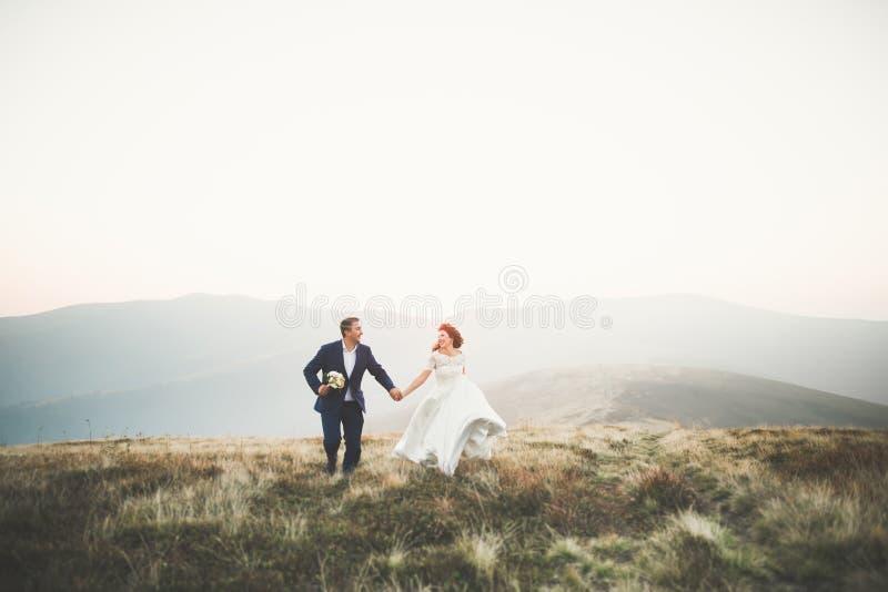 Pares hermosos de la boda que se besan y que abrazan cerca de la montaña con la visión perfecta foto de archivo