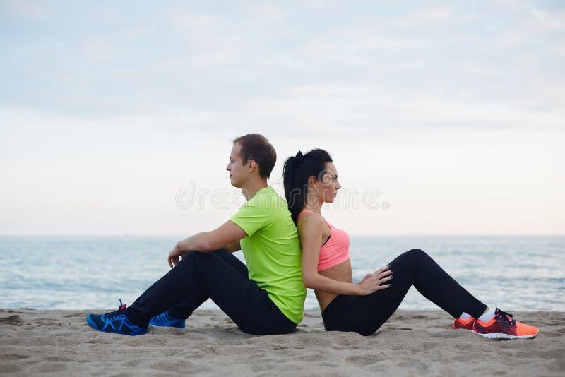 Pares hermosos de los atletas que descansan después del funcionamiento que se sienta en la costa imagen de archivo libre de regalías
