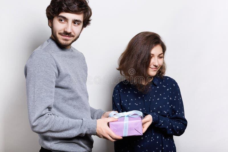 Pares hermosos de Younf con el presente en blanco Un individuo barbudo del inconformista que da a su novia un presente por un día fotografía de archivo libre de regalías