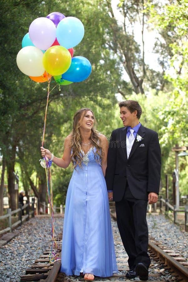 Pares hermosos del baile de fin de curso que caminan con los globos afuera imagenes de archivo