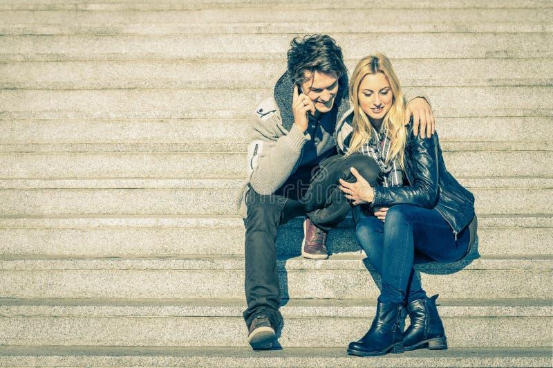 Pares hermosos del inconformista en el amor que tiene una llamada del smartphone imagenes de archivo