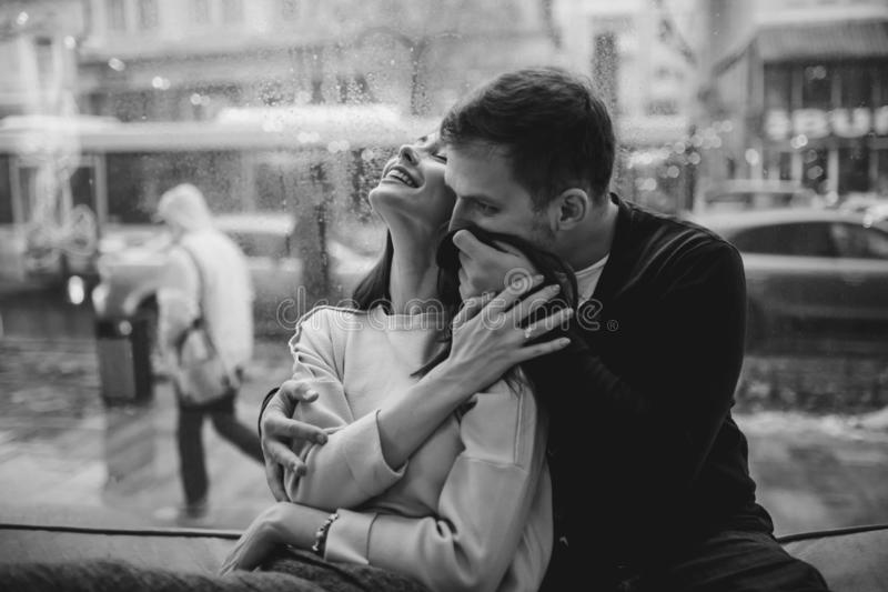 Pares hermosos El individuo de amor abraza a su novia encantadora que se sienta en el alféizar en un café acogedor Rebecca 36 foto de archivo