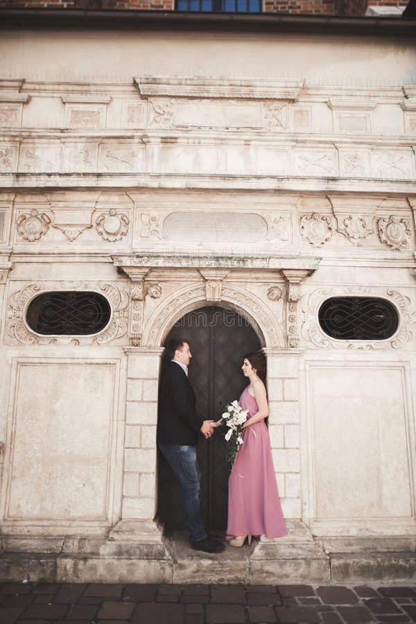 Pares hermosos elegantes de la boda que presentan cerca de una iglesia kraków imagen de archivo libre de regalías