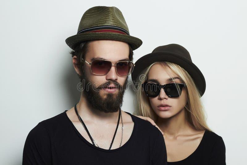 Pares hermosos en el sombrero que lleva los vidrios de moda juntos Muchacho y muchacha del inconformista fotos de archivo libres de regalías