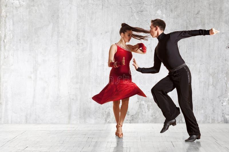 Pares hermosos en la danza de salón de baile activa en la pared fotos de archivo libres de regalías