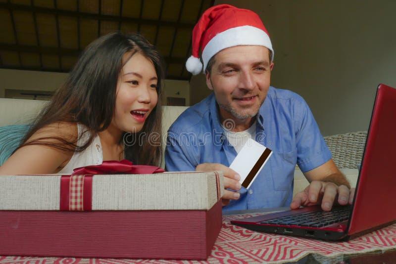Pares hermosos felices con la mujer china asiática atractiva y el marido blanco en el sombrero de Santa Christmas usando la tarje foto de archivo