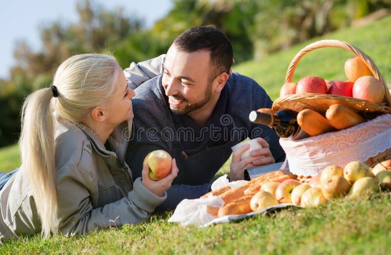 Pares hermosos jovenes cariñosos que charlan como teniendo comida campestre foto de archivo