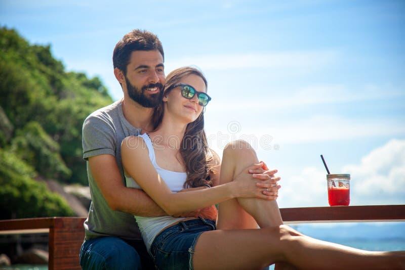 Pares hermosos jovenes en amor en el mar tropical en café de la playa, foto de archivo