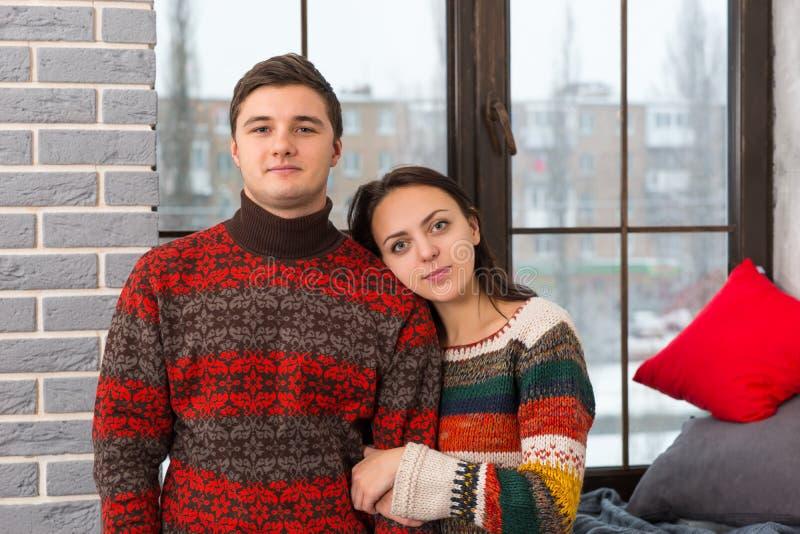 Pares hermosos jovenes en los suéteres hechos punto calientes que miran la c fotos de archivo libres de regalías
