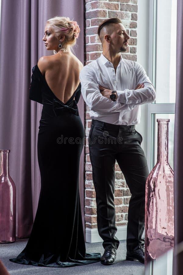 Pares hermosos jovenes en un traje y un vestido de noche imágenes de archivo libres de regalías