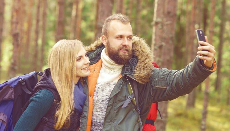 Pares hermosos jovenes que caminan en bosque y que toman el selfie en a foto de archivo libre de regalías