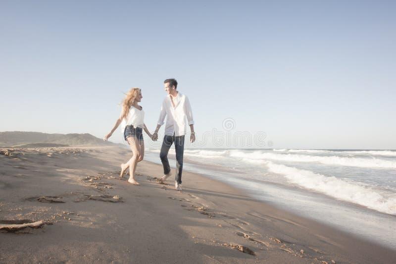 Pares hermosos jovenes que caminan feliz a lo largo de la playa junto imágenes de archivo libres de regalías
