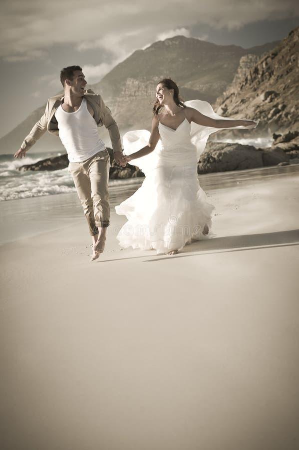 Pares hermosos jovenes que corren juguetónamente a través de la playa foto de archivo