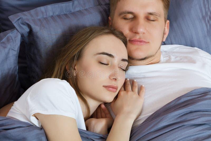 Pares hermosos jovenes que duermen en cama en la noche con los ojos cerrados - para cerrarse para arriba imagenes de archivo