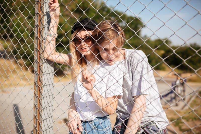 Pares hermosos jovenes que se colocan y que miran in camera a través de la cerca de la malla Muchacho alegre que abraza a la much foto de archivo