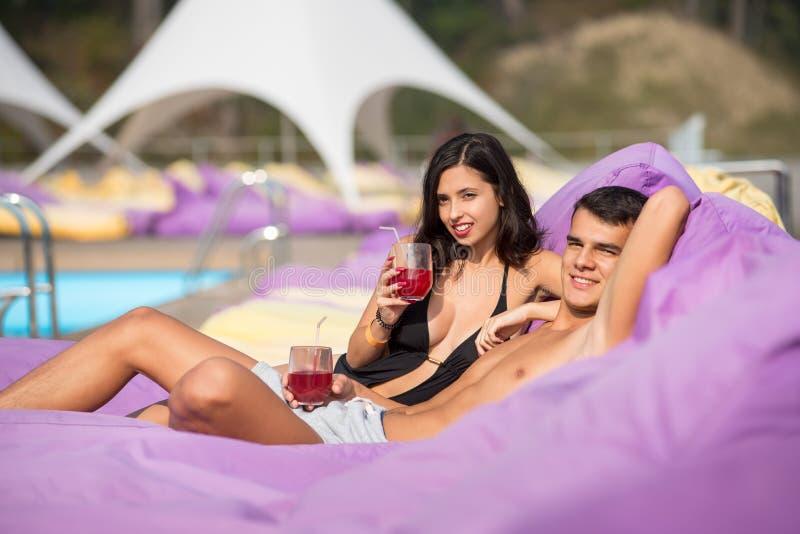 Pares hermosos - piscina cercana relajante del individuo y de la muchacha en ociosos amortiguados con las bebidas en el centro tu foto de archivo