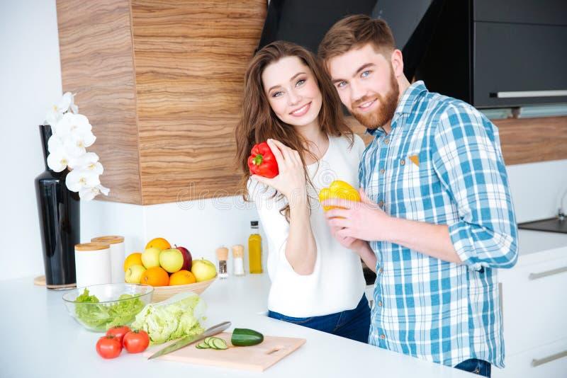 Pares hermosos que cocinan la comida sana en la cocina fotos de archivo libres de regalías
