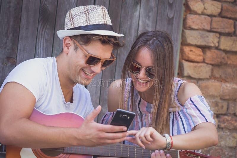 Pares hermosos que miran el teléfono elegante al aire libre fotografía de archivo