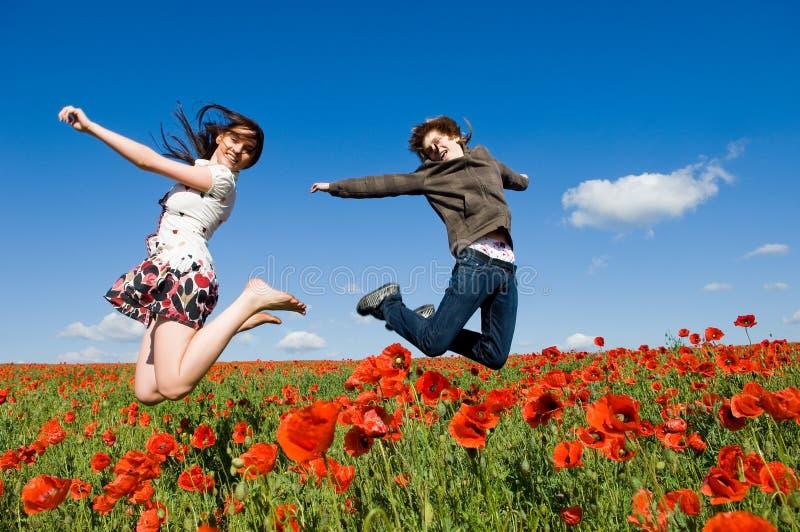 Pares hermosos que saltan en el campo de la amapola fotografía de archivo
