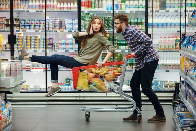 Pares hermosos que se divierten mientras que elige la comida en el supermercado imagen de archivo