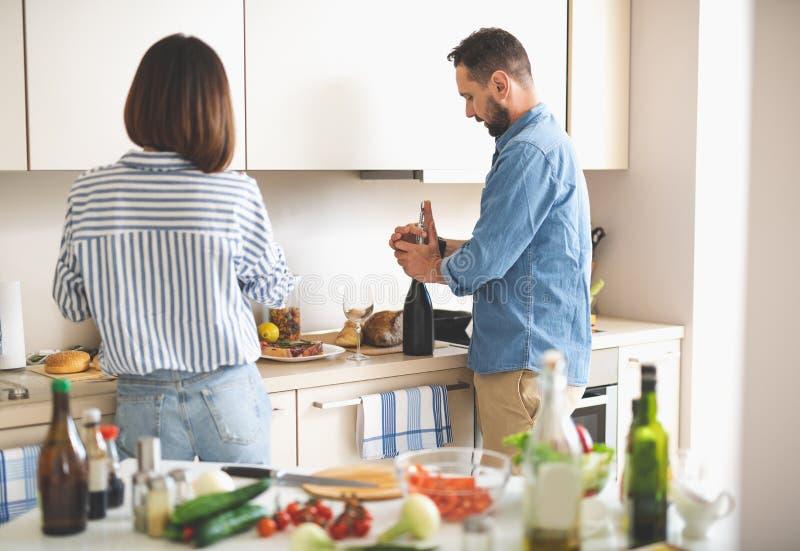 Pares hermosos que se preparan para la cena romántica en cocina foto de archivo libre de regalías