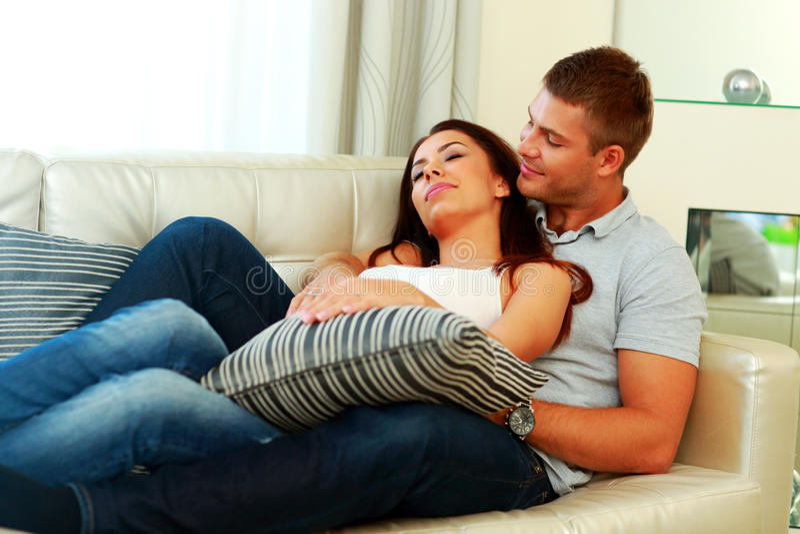 Pares hermosos que se relajan en el sofá fotos de archivo