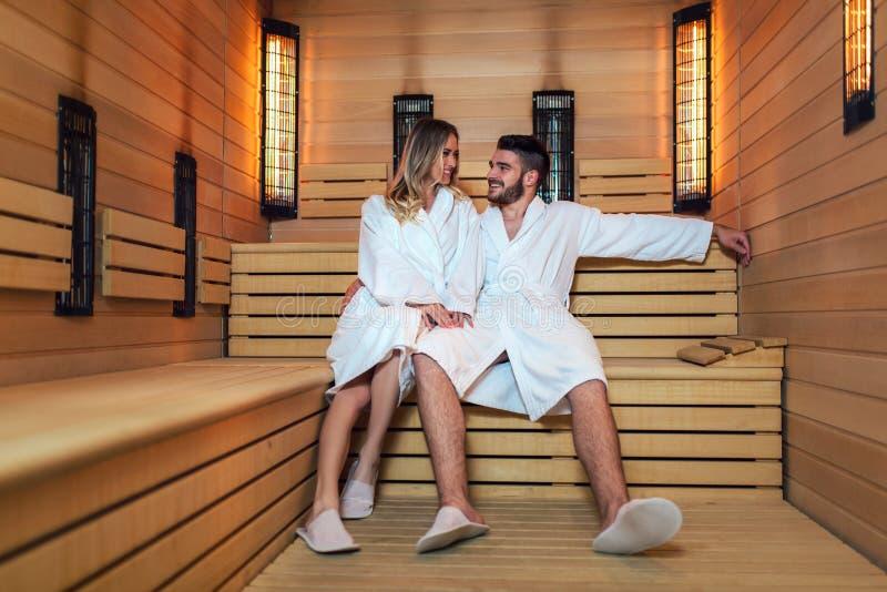 Pares hermosos que se relajan en la sauna infrarroja durante fin de semana de la salud imagenes de archivo
