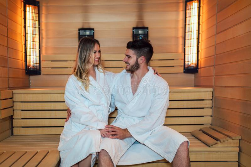 Pares hermosos que se relajan en la sauna infrarroja durante fin de semana de la salud imagen de archivo