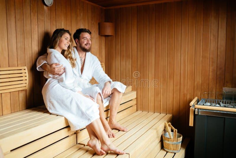 Pares hermosos que se relajan en sauna imagenes de archivo