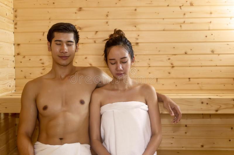 Pares hermosos que se relajan en sitio de la sauna del balneario fotos de archivo libres de regalías