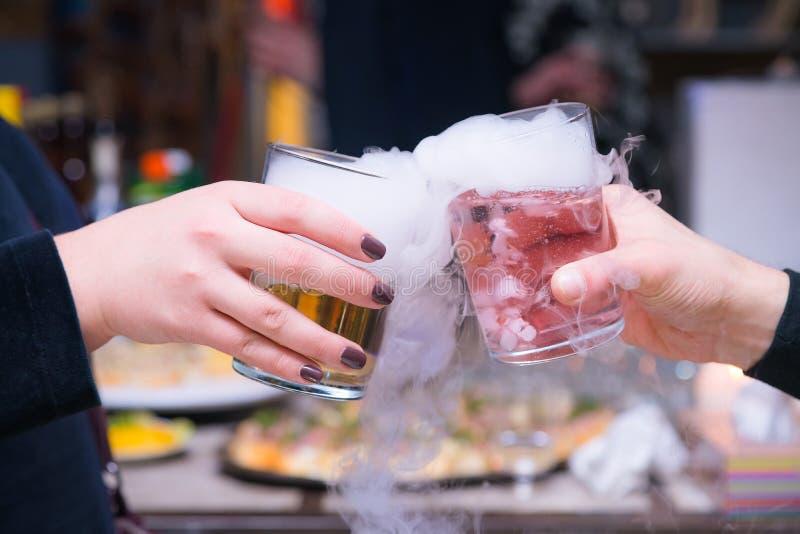 Pares hermosos que sostienen los c?cteles del hielo seco en la fiesta Bebida p?rpura con el vapor del hielo en el club, celebraci imagen de archivo libre de regalías