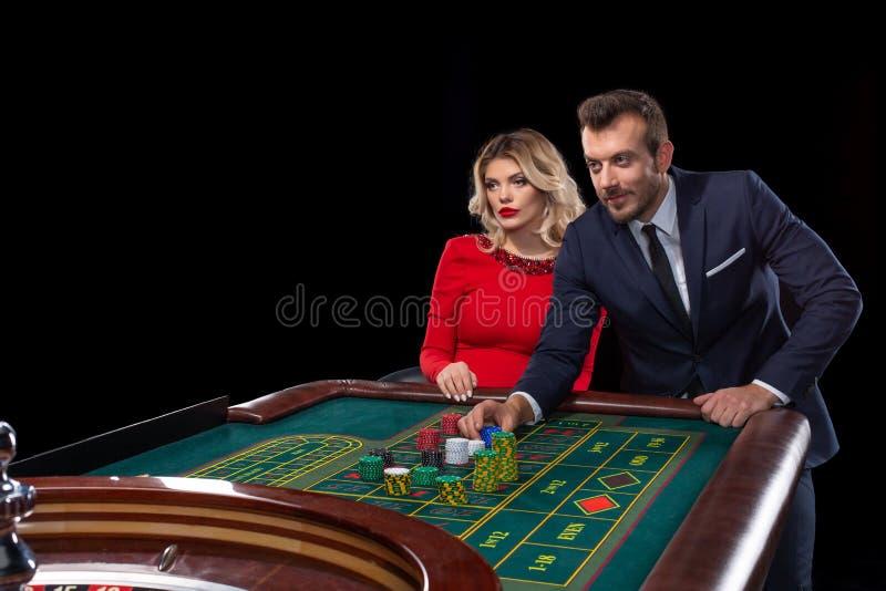 Pares hermosos y bien vestidos que juegan la ruleta en el casino imagenes de archivo
