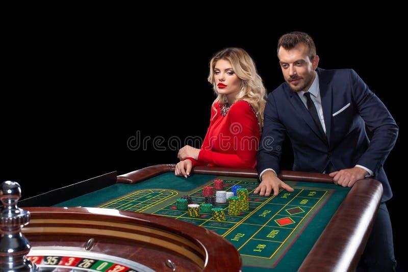 Pares hermosos y bien vestidos que juegan la ruleta en el casino fotografía de archivo libre de regalías