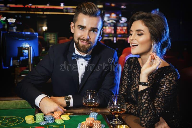 Pares hermosos y ricos que juegan la ruleta en el casino imagenes de archivo