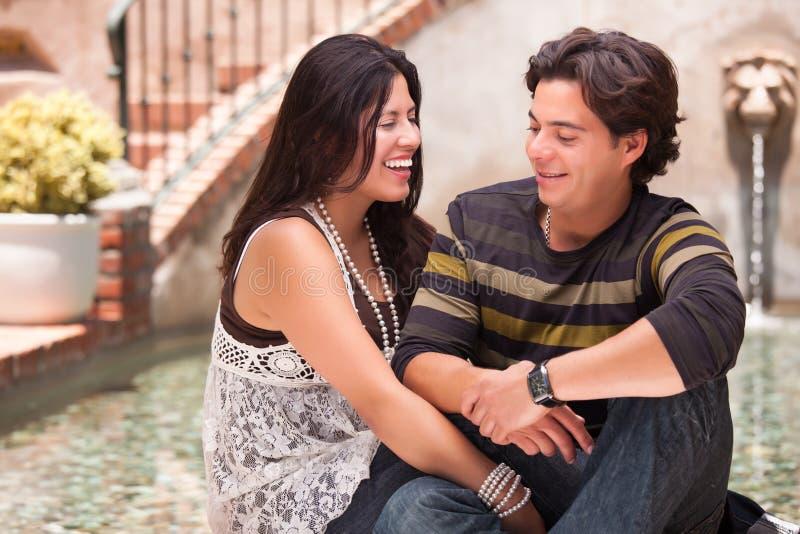 Pares hispánicos atractivos felices en una fuente imagen de archivo libre de regalías