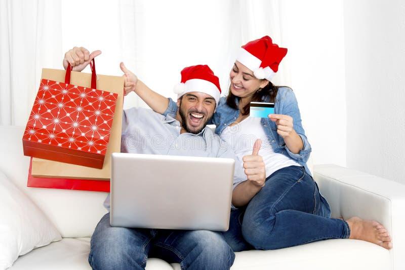 Pares hispánicos atractivos jovenes en compras en línea de la Navidad del amor con el ordenador foto de archivo