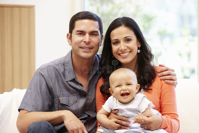 Pares hispánicos en casa con el bebé foto de archivo