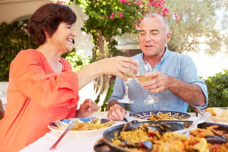 Pares hispánicos maduros que disfrutan de la comida al aire libre en casa fotografía de archivo