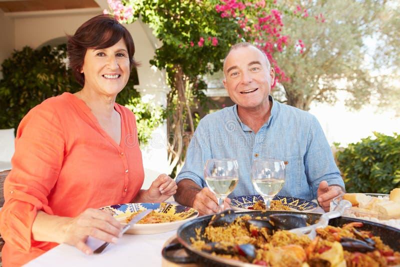 Pares hispánicos maduros que disfrutan de la comida al aire libre en casa imagen de archivo