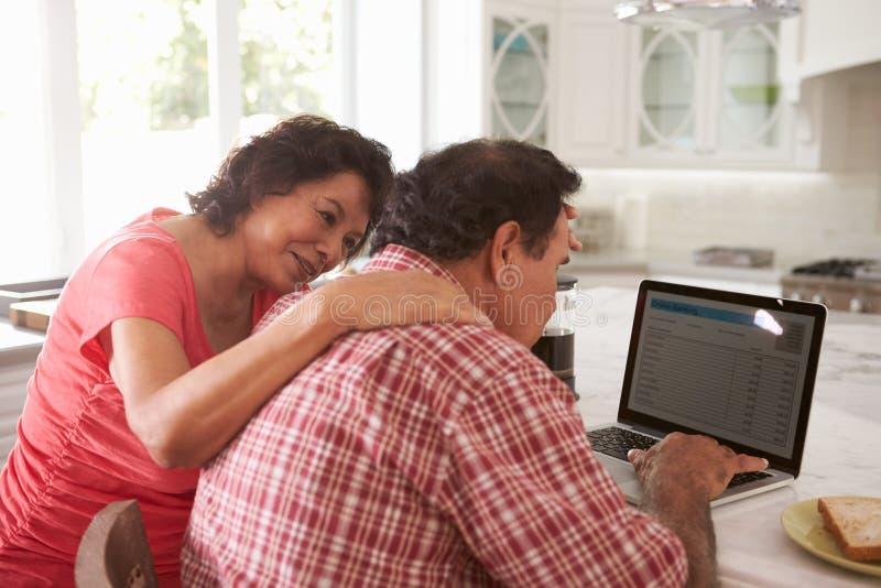 Pares hispánicos mayores confusos que se sientan en casa usando el ordenador portátil fotos de archivo