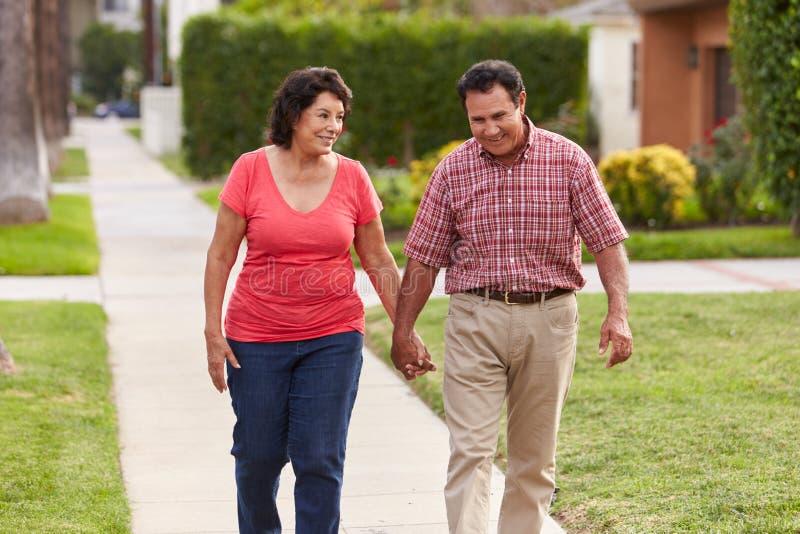 Pares hispánicos mayores que caminan a lo largo de la acera junto foto de archivo
